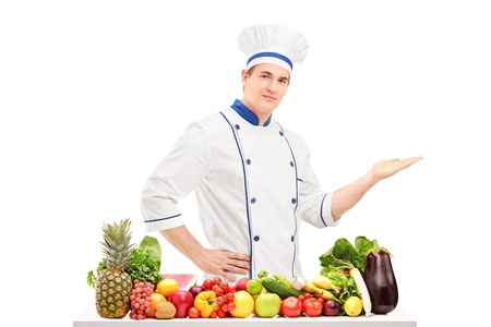 Male chef in a uniform gesturing with hand and posing behind a table full of fruits and vegetables, isolated on white background Stock Photo - 18751091