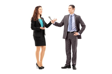 interviewing: Full length portrait of a businesswoman and male reporter having an interview isolated on white background Stock Photo
