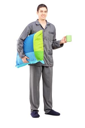 cansancio: Retrato de cuerpo entero de un hombre en pijama celebración de una almohada y una taza de café, aislados en fondo blanco