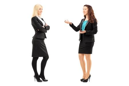 dos personas hablando: Retrato de cuerpo entero de una mujer joven profesional que tienen una conversación aislada en el fondo blanco Foto de archivo