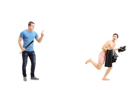 hombre desnudo: Retrato de cuerpo entero de un hombre violento que sostiene un bate de b�isbol y el hombre desnudo avergonzado en la ropa interior aislada en el fondo blanco Foto de archivo