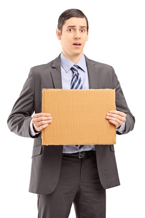 Upset young businessman in suit holding a piece of cardboard isolated on white background Stock Photo - 18751278
