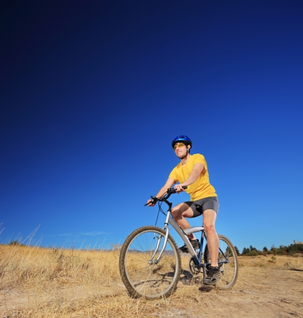 A young male with yellow shirt and helmet riding a mountain bike outdoors, shot with a tilt and shift lens Stock Photo - 18751216