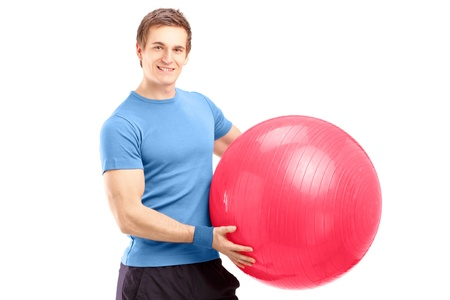 A young male athlete holding a pilates ball isolated against white background Stock Photo - 18882138