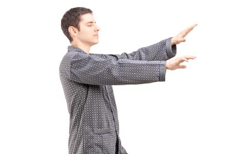 sleepwalking: A young man in pajamas sleepwalking isolated on white background