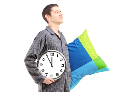 sleepwalker: A young man with pillow and clock sleepwalking isolated on white background