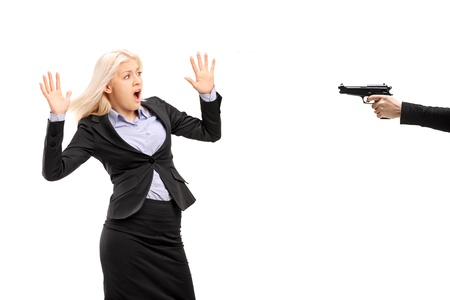 horrified: Afraid young businesswoman from a gun isolated on white background Stock Photo