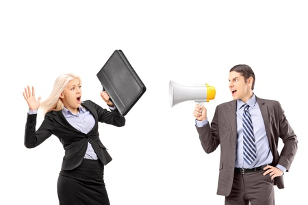 An afraid businesswoman and her manager shouting with a speakerphone isolated on white background Stock Photo - 18882043