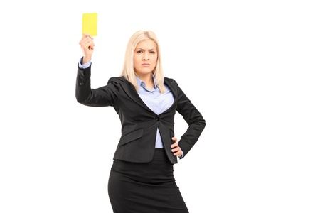 Angry businesswoman holding a yellow card isolated on white background photo