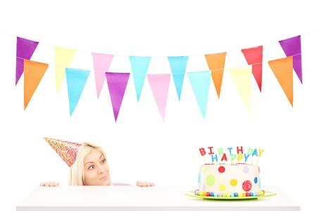 velas de cumpleaños: Muchacha del cumpleaños con un sombrero de fiesta buscando a un pastel de cumpleaños aislado en el fondo blanco