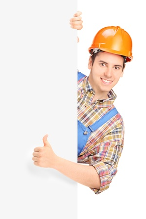 Construction worker posing and giving thumb up on a panel isolated against white background photo