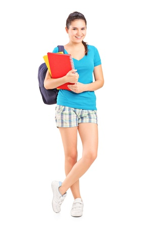Full length portrait of a female student with backpack holding notebooks isolated on white background photo