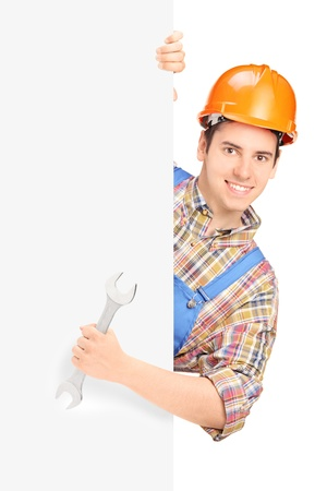 Young construction worker with helmet posing behind a panel and holding wrench isolated on white background photo