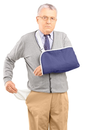 empty pockets: Poor man with broken arm showing his empty pocket, isolated on white background