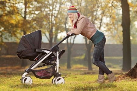 babysitter: A young mother with a baby carriage walking in a park