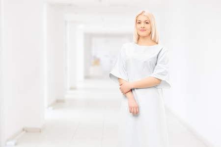 recovering: Female patient wearing hospital gown and posing in a hospital corridor Stock Photo