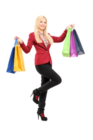 Full length portrait of a blond smiling woman holding shopping bags isolated against white background Stock Photo - 18909252