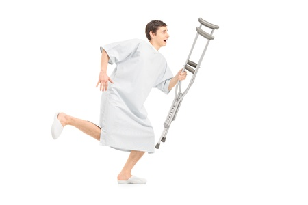hospital gown: Full length portrait of a male patient running and holding a crutch, isolated on white background