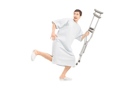 operation gown: Full length portrait of a male scared patient running and holding a crutch, isolated on white background