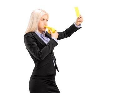 Empresaria joven que sopla un silbato y mostrando una tarjeta amarilla, aislados en fondo blanco