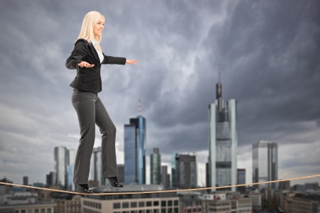 Young businesswoman walking on a rope, with the financial centre in Frankfurt, Germany in the background Stock Photo - 18918127