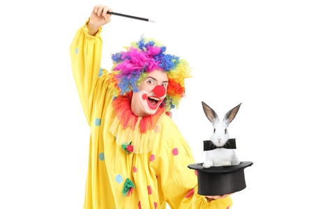 A circus clown performing a magic trick with a top hat and a rabbit isolated on white background photo