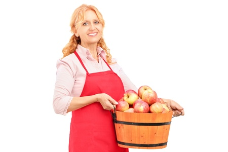 A woman with apron holding a bucket full of apples isolated on white background photo
