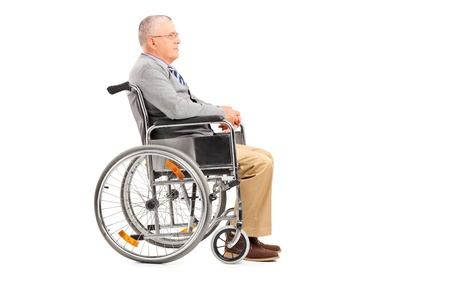 paraplegia: A disabled senior gentleman posing in a wheelchair isolated on white background