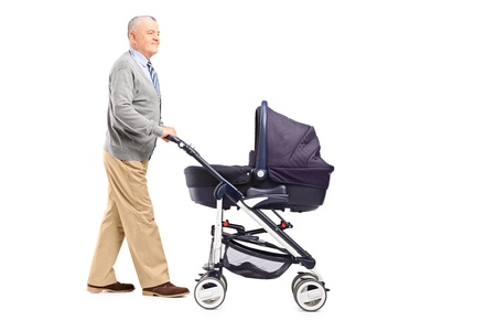 pram: Full length portrait of a grandfather pushing his baby nephew in a stroller isolated on white background