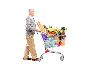 empujando: Integral potrait de un caballero empujando un carrito de compras lleno de tiendas de comestibles aisladas sobre fondo blanco