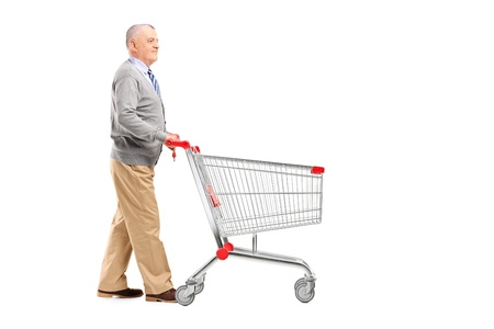 empty shopping cart: Full length potrait of a gentleman walking and pushing an empty shopping cart isolated on white background Stock Photo
