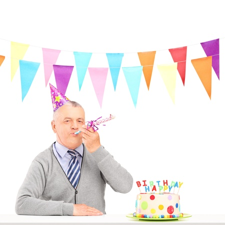 one adult: A happy mature man with party hat blowing and a birthday cake isolated on white background