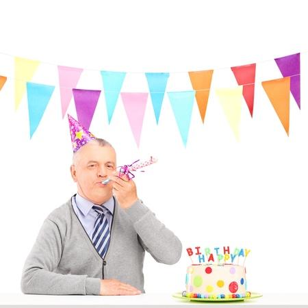 mature adult men: Un uomo maturo felice con cappello di partito che soffia e una torta di compleanno isolati su sfondo bianco Archivio Fotografico
