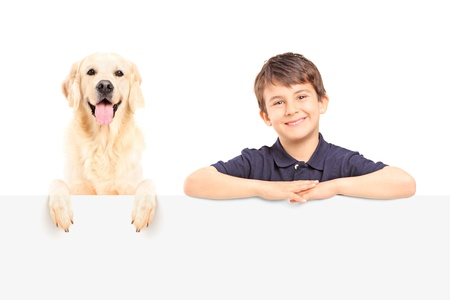 A smiling boy and Labrador retriever posing behind a blank panel photo