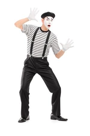 pantomima: Retrato de cuerpo entero de un mimo masculino que se realiza, aislado en fondo blanco Foto de archivo