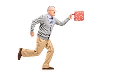 late 50s: Full length portrait of a mature gentleman running with a gift bag, isolated on white background
