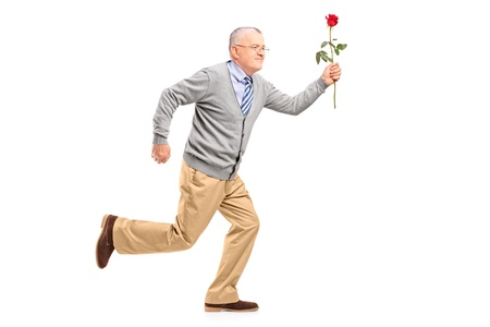 late 50s: Full length portrait of a mature gentleman running with a red rose, isolated on white background Stock Photo