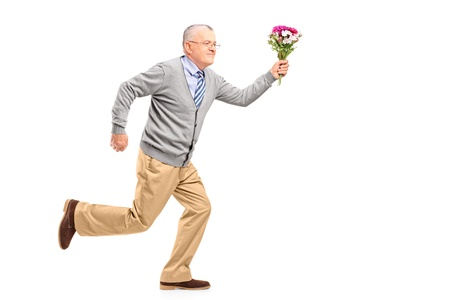 late 50s: Full length portrait of a mature gentleman running with flowers, isolated on white background Stock Photo