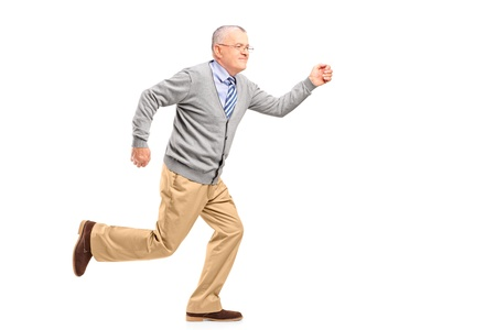 late 50s: Full length portrait of a mature gentleman running, isolated on white background Stock Photo