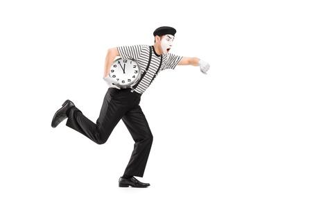 pantomima: Retrato de cuerpo entero de un mimo que sostiene un reloj y llegando tarde, aislado en fondo blanco