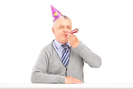 Happy birthday mature man with party hat blowing isolated against white background photo