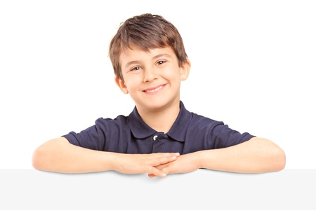 Little smiling boy standing behind a blank panel isolated on white background Stock Photo - 19122436