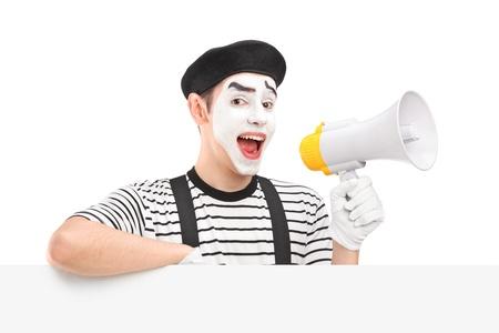 pantomima: Hombre mimo sosteniendo un altavoz y que presenta en un panel en blanco, aislados en fondo blanco