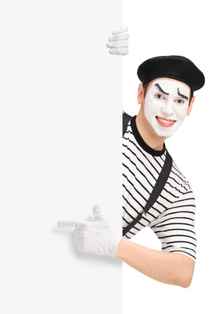 Mime artist pointing on a blank panel, isolated on white background photo