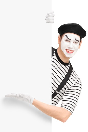 pantomima: Varón sonriente mimo que muestra en un panel, aislado en fondo blanco