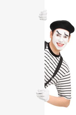 mimic: Smiling mime artist posing behind a blank panel, isolated on white background