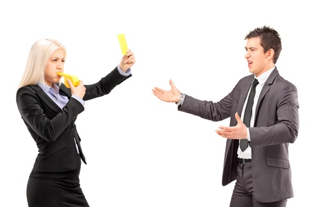whistles: Woman in business suit showing a yellow card and blowing a whistle to a man in a business suit, isolated on white background Stock Photo
