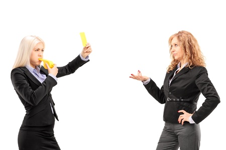 Woman in suit showing a yellow card and blowing a whistle to a female colleague, isolated on white background photo