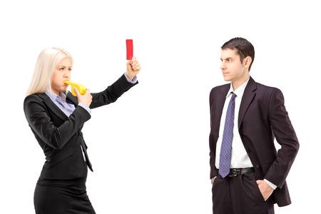 Young woman in a suit showing a red card and blowing a whistle to a young businessman, isolated on white background