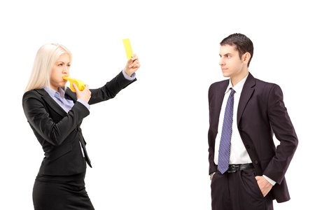 Young woman in a suit showing a yellow card to a young businessman, isolated on white background photo